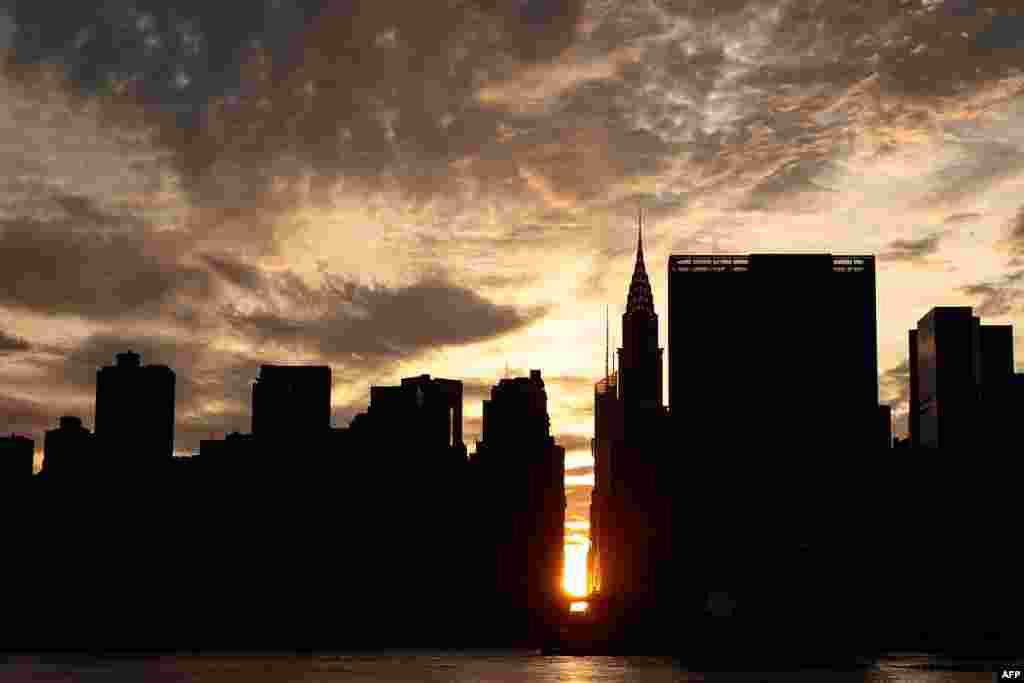 Pemandangan matahari terbenam di Manhattan, New York yang dikenal sebagai 'Manhattanhenge' dari Hunters Point South Park, di Queens borough, New York.