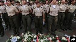 Guardias nacionales bolivarianas ante ofrendas florales por los muertos en los disturbios venezolanos.
