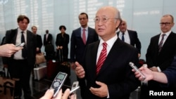 International Atomic Energy Agency Director General Yukiya Amano talks to the media as he arrives at Vienna's airport, Austria, Aug. 18, 2014.