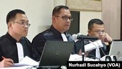 Jaksa Taufiq Ibnugroho membaca barang bukti buku yang memuat pengumpulan dana dari kontraktor terkait kasus suap di Yogyakarta. (Foto: VOA/Nurhadi Sucahyo)