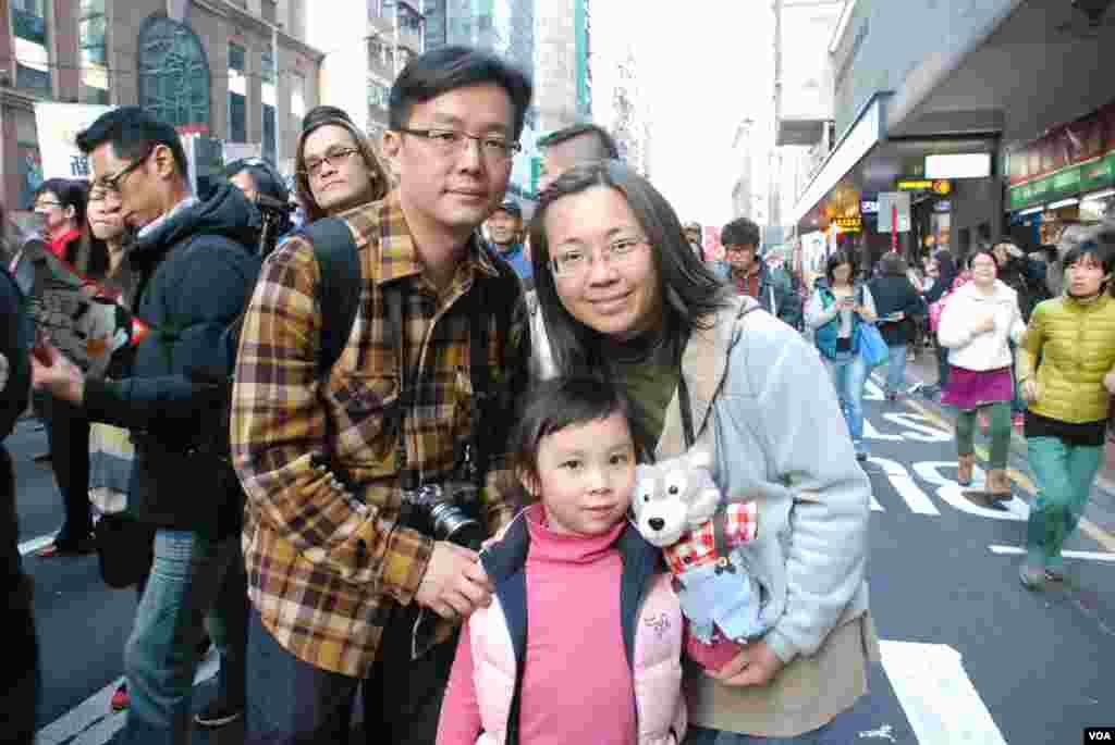 父母帶著女兒參與遊行,女兒手持模仿「路福西」的公仔