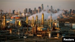 FILE - The Philadelphia Energy Solutions oil refinery is seen at sunset in front of the Philadelphia skyline in Pennsylvania, March 24, 2014.