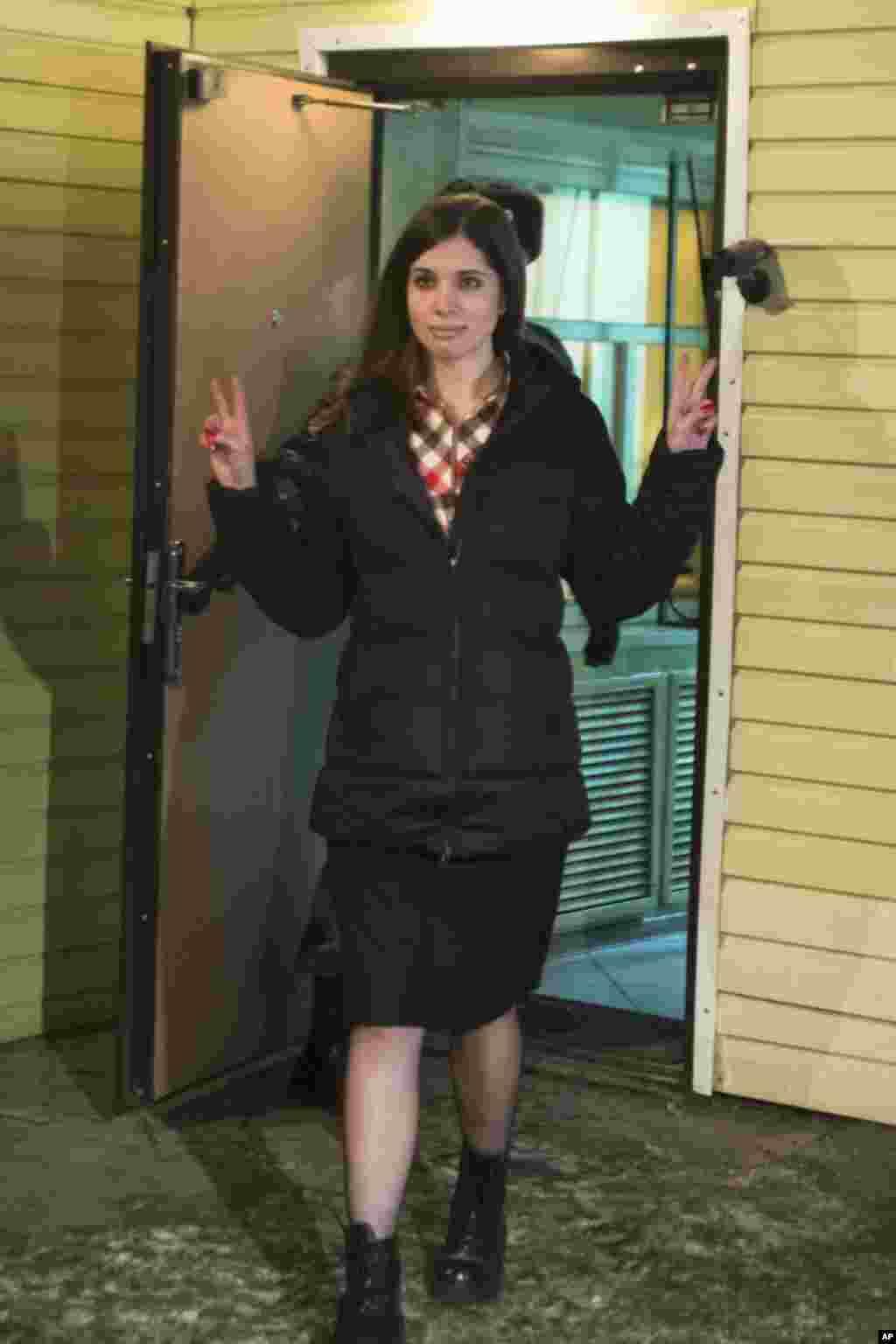 Nadezhda Tolokonnikova mengacungkan jari tanda damai saat ia meningalkan penjara di Krasnoyarsk, Rusia, Senin (23/12). (AP/Tatyana Vishnevskaya)