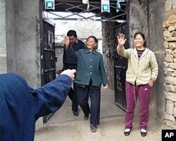 陈光诚母亲和妻子。陈母背后的男人被网友指认是保安