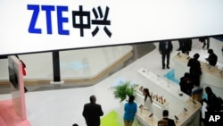 FILE - People are seen gathered at a ZTE company booth at the Mobile World Congress in Barcelona, Spain, Feb. 26, 2014.