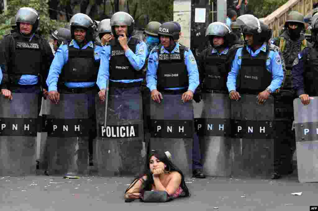 Salvador Nasralla, s supporter of the presidential candidate for the Honduran Opposition Alliance Against the Dictatorship, lies on the street in front of police officers during a demonstration against the contested re-election of of President Juan Orlando Hernandez, in Tegucigalpa, Jan. 21, 2018.