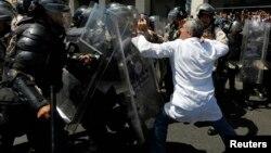 La policía reprime a un médico durante una marcha antigubernamental en Caracas.