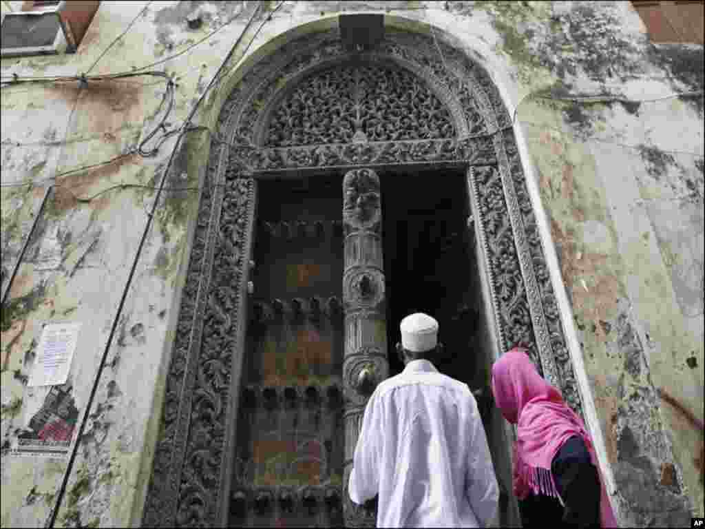 Muslim faithfuls enter a building in the historic centre of Stone Town in the Indian Ocean Island of Zanzibar
