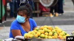 Archivo - Una mujer usa una máscara facial mientras espera clientes en un mercado en Tegucigalpa.