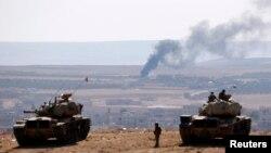 Tentara Kurdi dengan tank di sisi perbatasan Turki menyaksikan asap mengepul dari kota Kobani di Suriah (8/10). (Reuters/Umit Bektas)