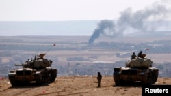 FILE - Turkish army tanks are seen on Turkey's border with Syria, Oct. 8, 2014.