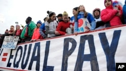 FILE - Fans stand behind a sign for equal pay for the women's soccer team during a match between the United States and Colombia, in East Hartford, Conn., April 6, 2016. The World Economic Forum's annual Global Gender Gap Report released, Oct. 25, 2016, found that the global gender pay gap will not be closed for another 170 years if current trends continue.