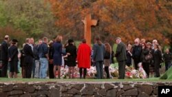 FILE - Families and friends are seen gathered around a memorial at a service in memory of 35 people killed, on the first anniversary of a rampage by a lone gunman in Port Arthur, Tasmania, Australia, April 28, 1997.