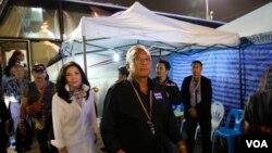 Pemimpin demonstrasi anti-pemerintah Suthep Thaugsuban (depan) bersama istrinya Srisakul Promphan (berbaju putih) tiba di monumen Demokrasi di Bangkok, Thailand (15/12). (AP/Manish Swarup)