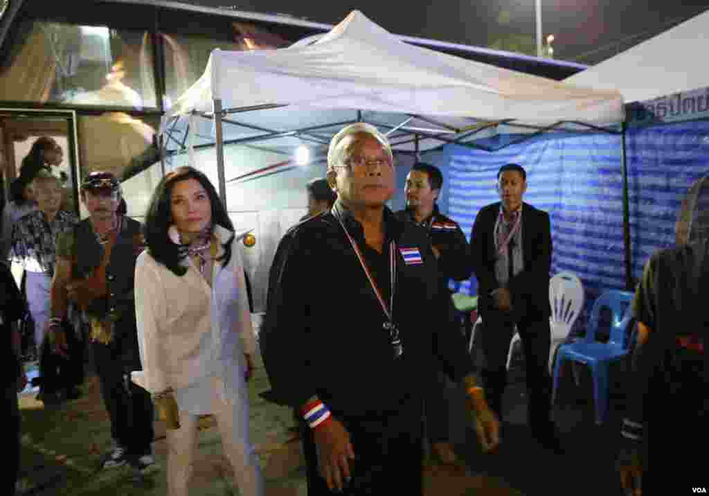 Anti-government protest leader Suthep Thaugsuban, center, with his wife Srisakul Promphan, in white, arrives at the Democracy monument, in Bangkok, Thailand, Dec. 15, 2013.