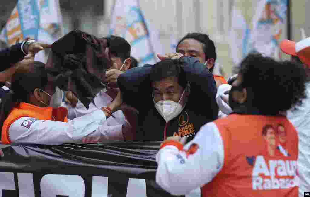 """Andres Arauz, presidential candidate for the alliance """"Unidos por la Esperanza"""" reacts after being struck in the head by an object during a rally in Quito, Ecuador, Jan. 26, 2021."""