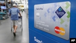 FILE - A customer walks past a sign promoting Sam's Club MasterCard credit cards at a Sam's Club store store in Bentonville, Ark., June 4, 2015.