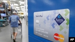 Seorang konsumen berjalan melalui iklan kartu kredit Sam's Club MasterCard di Bentonville, Arkansas, 4 Juni 2015.