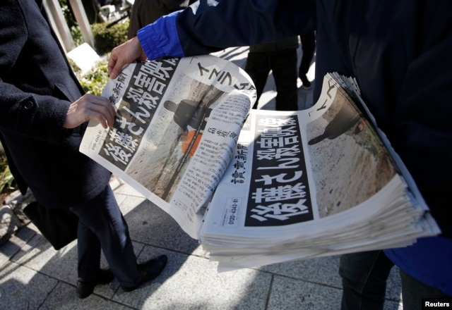 A man, left, receives an extra edition of a newspaper, which reports that Islamic State militants said they had beheaded Japanese journalist Kenji Goto, in Tokyo, Feb. 1, 2015.