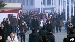 En esta captura de video, peatones desafían el frío mientras se abren camino a través de una plaza abierta, el jueves 30 de enero de 2020, en Pyongyang, Corea del Norte.