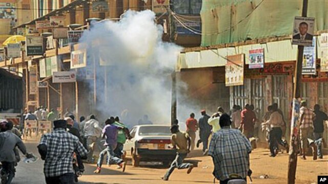 Ugandan protesters run after police fired tear gas during a demonstration against high food and fuel prices, in Kampala, Uganda, October 17, 2011.
