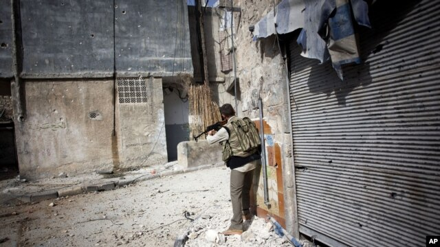 A Free Syrian Army fighter fires his weapon toward Syrian Army positions in Karmal Jabl district in Aleppo, Syria, Oct. 21, 2012.