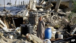 FILE - A man stands in the rubble off a home demolished by security forces on the on the Egyptian side of border town of Rafah, northeast of Cairo, Egypt.