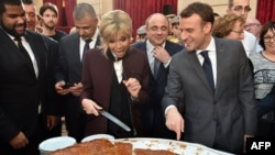 French President Emmanuel Macron and his wife Brigitte cut slices of a traditional epiphany cake during a ceremony at the Elysee palace, Paris, Jan. 12, 2018.