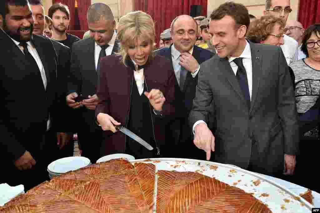 ប្រធានាធិបតីបារាំងEmmanuel Macron និងភរិយារបស់លោកគឺលោកស្រីBrigitte កំពុងកាត់នំខេកប្រពៃណី នៅក្នុងពិធីមួយនៅរាជវាំងElysee ក្នុងទីក្រុងប៉ារីស។