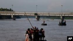 Migrants cross by raft from Tecun Uman, Guatemala, left, to Ciudad Hidalgo, Mexico, on June 14, 2019.