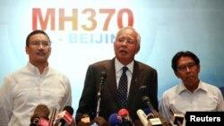 PM Malaysia Najib Razak (tengah), didampingi Menteri Transportasi Hishammuddin Hussein (kiri) dan Dirjen Penerbangan Sipil Azharuddin Abdul Rahman (kanan) menyampaikan keterangan di Bandara Internasional Kuala Lumpur (15/3).