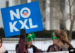 FILE - Two women wearing sunglasses with a tree design join other opponents of the Keystone XL pipeline to celebrate President Barack Obama's veto of legislation pertaining to the project outside the White House in Washington, Feb. 24, 2015.
