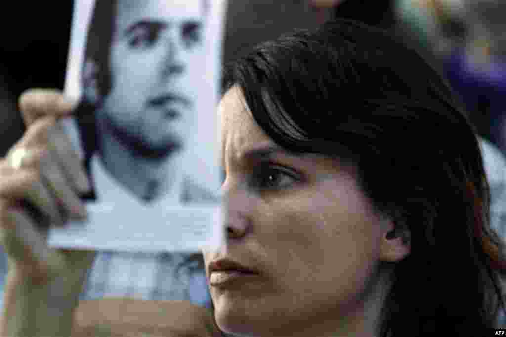 The relative of a victim killed during Argentina's dirty war holds his picture as she listens to the sentence for former dictator Jorge Videla in Cordoba, Argentina, Wednesday Dec. 22, 2010. Videla was sentenced to life in prison Wednesday for the tortur