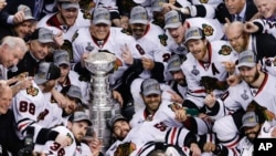 The Chicago Blackhawks pose with the Stanley Cup after beating the Boston Bruins 3-2 in Game 6 of the NHL hockey Stanley Cup Finals, June 24, 2013, in Boston.