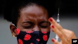 Reaksi seorang perempuan melihat suntikan vaksin COVID-19 buatan Sinovac, di pinggiran negara bagian Goias, Brazil, 16 Maret 2021.