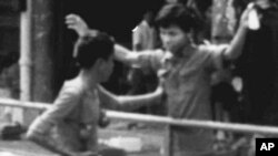 A Khmer Rouge rebel frisks a civilian in downtown Phnom Penh hours after the rebel forces led by Pol Pot took control of the Cambodian capital April 17, 1975.