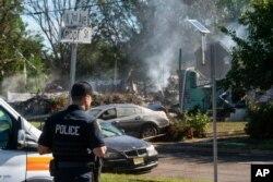 Seorang petugas polisi menjaga sisa-sisa rumah yang meledak, kemungkinan karena masalah saluran gas yang disebabkan oleh banjir parah dari Badai Tropis Ida, di Manville, New Jersey, 3 September 2021. (Foto: AP)