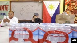 Terrence Valen, president of the National Alliance for Filipino Concerns, center, talks on the phone next to Joey Elacion as they sit behind bottles of water donated by Elacion for victims of Typhoon Haiyan, at the Filipino Community Center in San Francisco, Nov. 11, 2013.