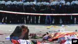 Polislerin beklediği alanın hemen ötesinde üstü örtülü cesetlerin yanı başında ağlayan bir kişi