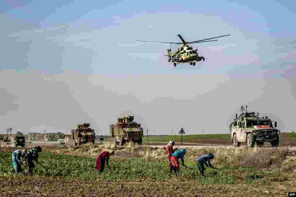 A Russian Mil Mi-17 military helicopter flies over a joint Russian-Turkish military patrol convoy in the countryside near Darbasiyah, along the border with Turkey in Syria's northeastern Hasakah province.