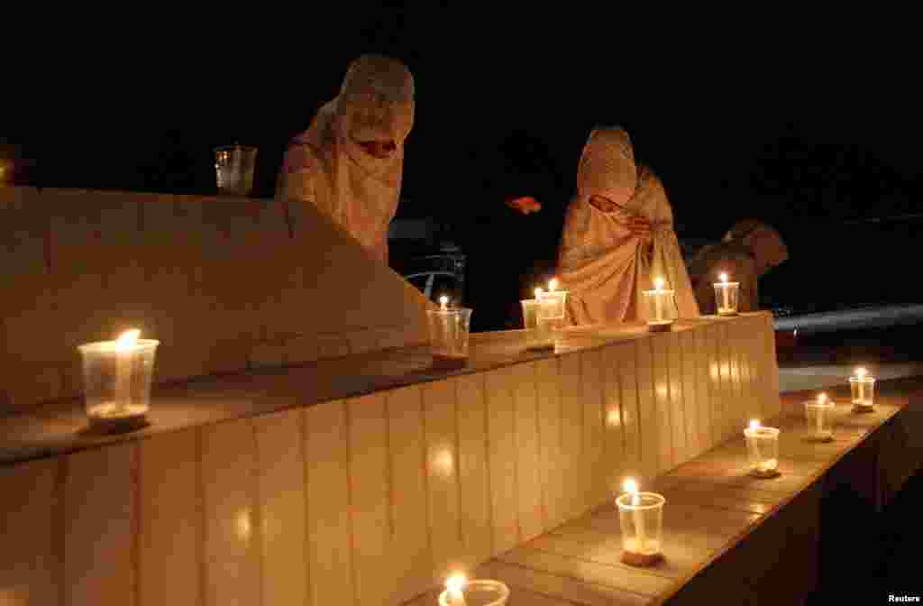 Women light candles during a candlelight vigil in honor of philanthropist Abdul Sattar Edhi in Quetta, Pakistan.