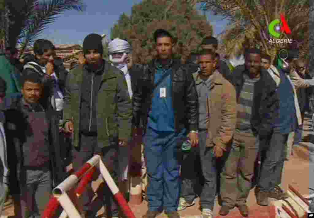 Unidentified former hostages pose for the media in Ain Amenas, Algeria, in this image taken from television , January 18, 2013. (Canal Algerie)