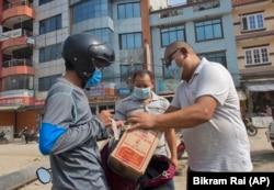 Sherpa, center, delivers food to fellow guides in Kathmandu, Nepal, Monday, June 7, 2021. (AP Photo/Bikram Rai)