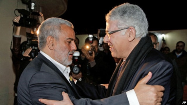 Morocco's newly-appointed moderate Islamist Prime Minister Abdelilah Benkirane (L) greets outgoing Prime Minister Abbas Fassi at the Justice and Development Party headquarters in Rabat, Morocco, November 30, 2011.