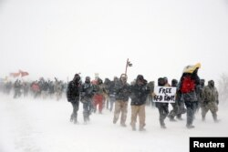 "FILE - Veterans join activists in a march just outside the Oceti Sakowin camp during a snow fall as ""water protectors"" continue to demonstrate against plans to pass the Dakota Access pipeline adjacent to the Standing Rock Indian Reservation, near Cannon Ball, North Dakota, Dec. 5, 2016."