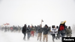 "Veterans join activists in a march just outside the Oceti Sakowin camp during a snow fall as ""water protectors"" continue to demonstrate against plans to pass the Dakota Access pipeline adjacent to the Standing Rock Indian Reservation, near Cannon Ball, North Dakota."