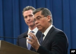 FILE - California Attorney General Xavier Becerra (R), accompanied by Gov. Gavin Newsom, announce their intent to sue the Trump administration over an emergency declaration to fund a border wall, Feb. 15, 2019, in Sacramento, California.
