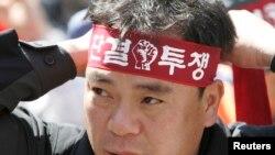 Seorang pekerja serikat buruh di perusahaan kereta milik negara, KORAIL, demo di stasiun kereta di Seoul.