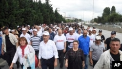 "Kemal Kilicdaroglu,foreground, second left, the leader of Turkey's main opposition Republican People's Party, walks with thousands of supporters on the 20th day of his 425-kilometer (265-mile) "" march for justice "" in Izmit, Turkey, Tuesday, July 4, 2017."