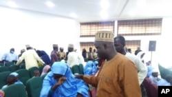 FILE - A freed student of Salihu Tanko Islamic School is reunited with her father in Minna, Nigeria, Aug 27, 2021.